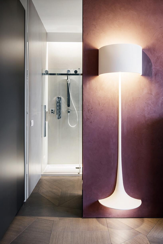 elegancki penthouse od Zaha Hadid wyjątkowa łazienka zfioletową ścianą izamontowaną na nią lampą ze świecącą podstawką