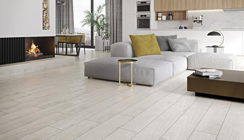jasny salon zkominkiem ipłytkami podłogowumi przypominającymi panele drewnianem
