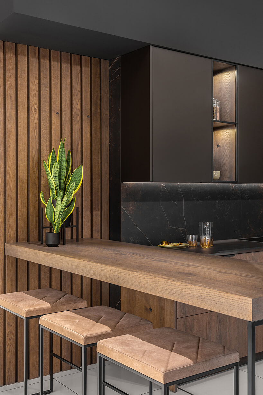 ekskluzywna kuchnia ernestrust zdrewnianym blatem itrzema stołkami przy ciemnej kuchni