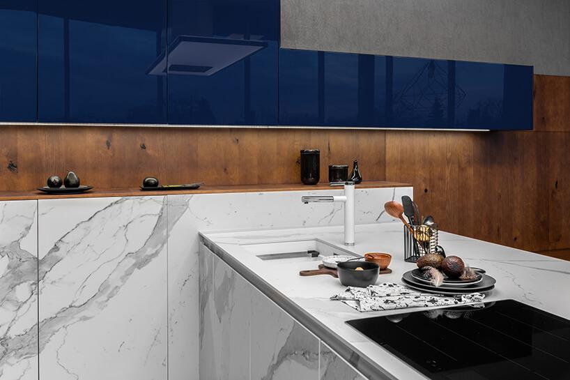 ekskluzywna kuchnia ernestrust zbiałymi frontami brązowymi iniebieskimi wiszącym szafkami