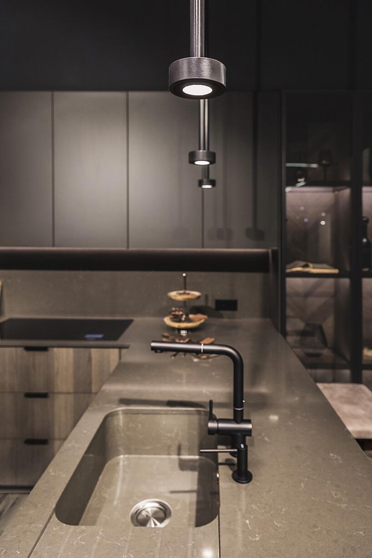 ekskluzywna kuchnia ernestrust ciemna kuchnia zkamiennym blatem izlewozmywakiem iczarną matową wylewką