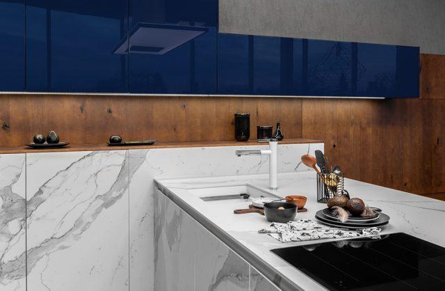ekskluzywna kuchnia ernestrust z białymi frontami brązowymi i niebieskimi wiszącym szafkami