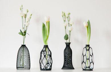 cztery wazony z czarnego plastiku z pojedynczymi kwiatkami