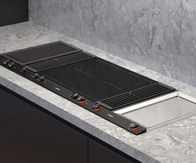 czarny grill elektryczny Gaggenau Vario, wentylacja blatowa ipłyty grzewcze Teppan Yaki wjasnym kamiennym blacie kuchennym