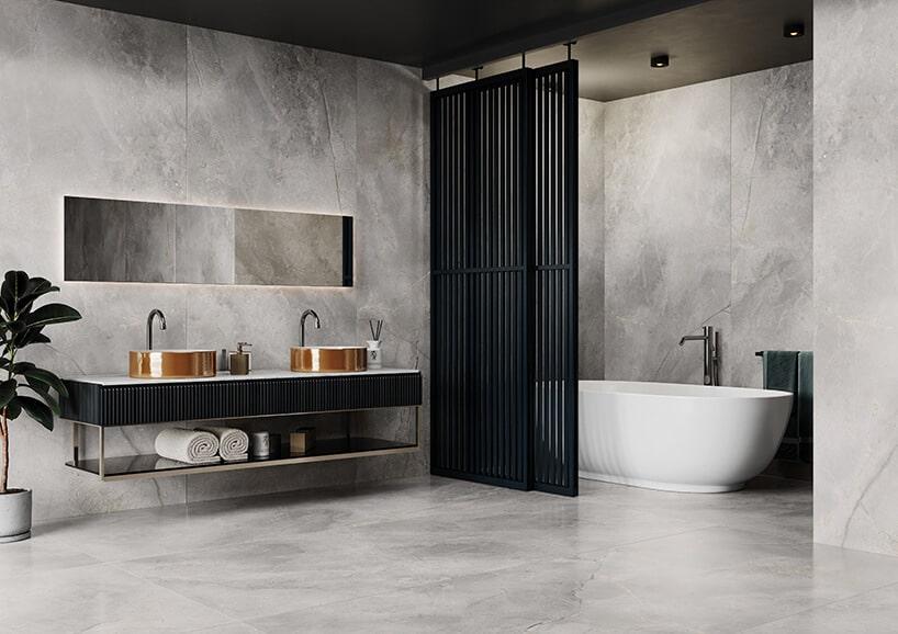 łazienka zmetalową ścianką wkolorze czarnym odgradzającą wannę przy betonowych kaflach zbiałymi wzorami oraz miedzianymi umywalkami