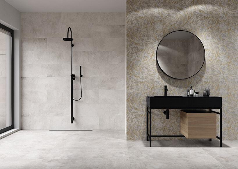 okrągłe lustro wczarnej oprawie na ścianie zlekkim wzorem tapery oraz czarnym prysznicem