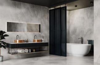łazienka z metalową ścianką w kolorze czarnym odgradzającą wannę przy betonowych kaflach z białymi wzorami oraz miedzianymi umywalkami