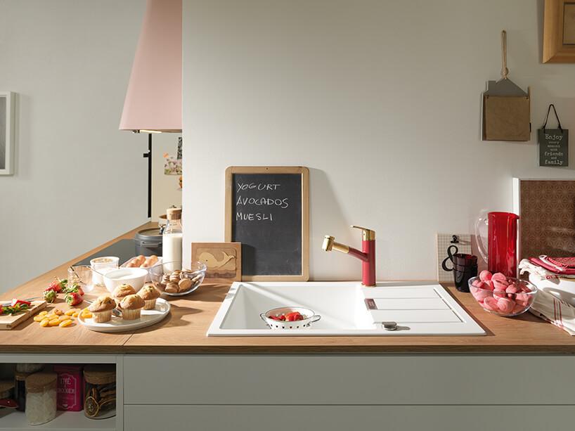 biały nowoczesny zlewozmywak SIRIUS zkolekcji TECTONITE od Franke zczerwono-złotą baterią kuchenną wdrewnianym blacie kuchennym