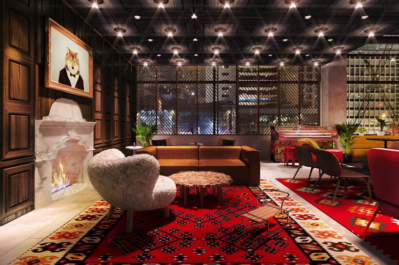 lobby hotelu ibis Styles Sarajewo zdużym dywanem, kominkiem iobrazem lisa wgarniturze