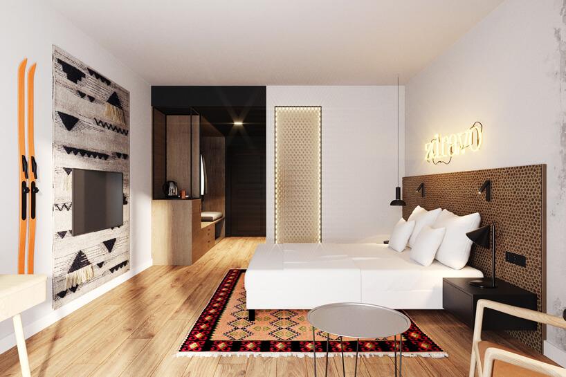 jasne wnętrze pokoju hotelowego zdrewnianą podłogą inartami na ścianie