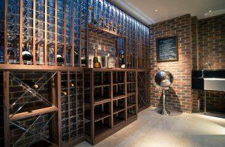 piwniczka na wino z regałem z drewna i plexiglasu na tle ceglanej ściany