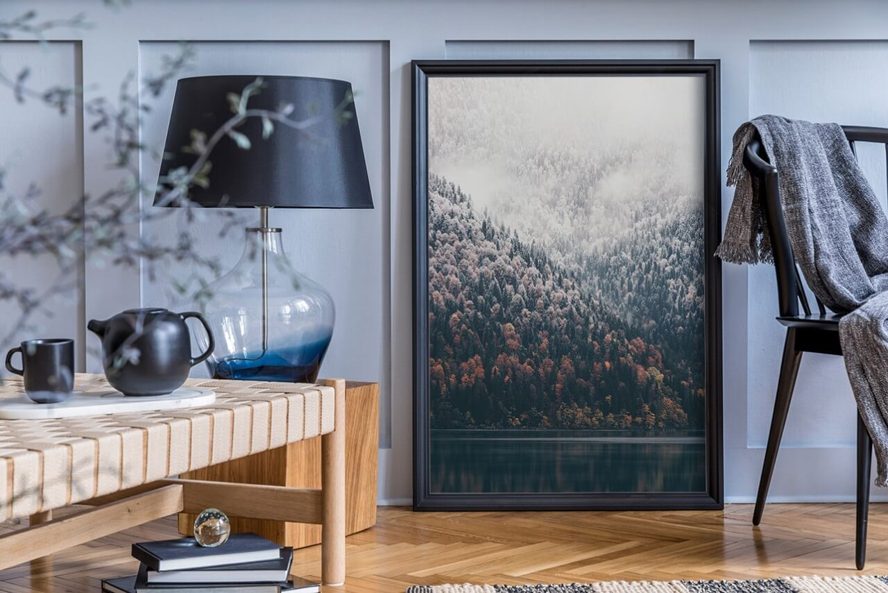 plakat wramie oparty ościanę pokoju, zlampą stojącą na stole na pierwszym planie