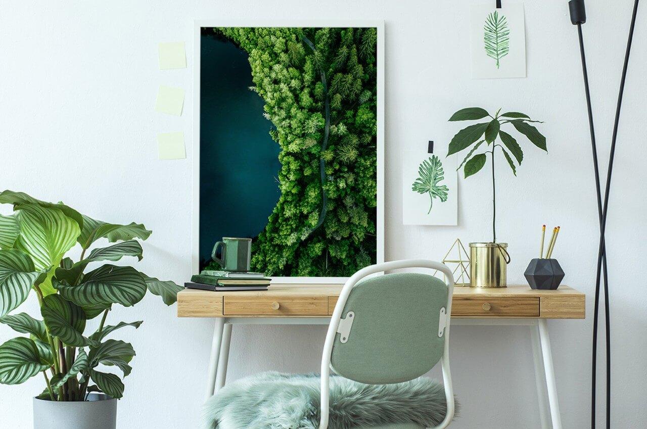 plakat zlasem oparty obiurko, na którym znajdują się rośliny idodatki