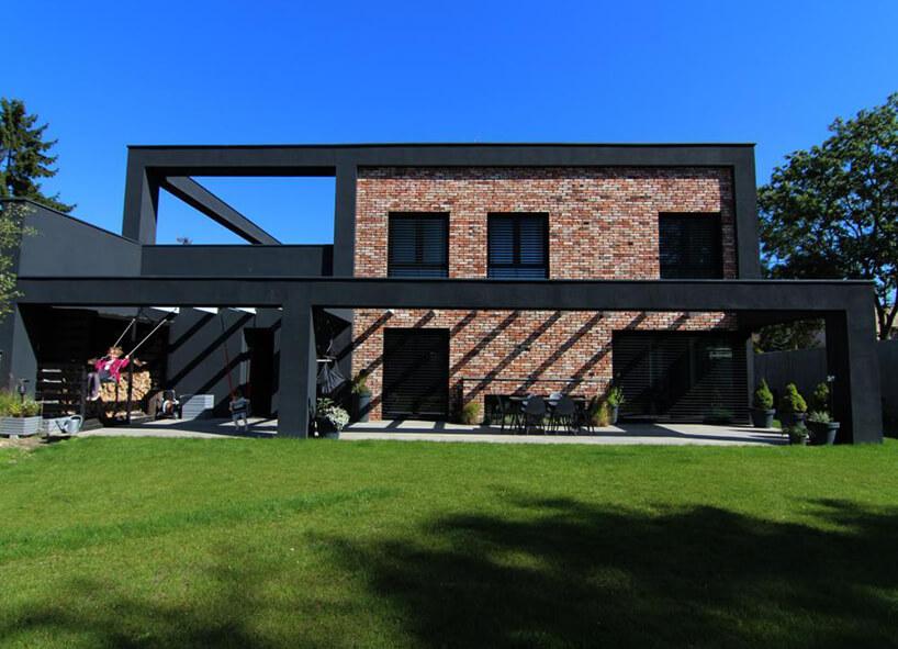 nietypowy dom wspartym na czarnych elementach zceglaną ścianą od Biura Awinci Architects
