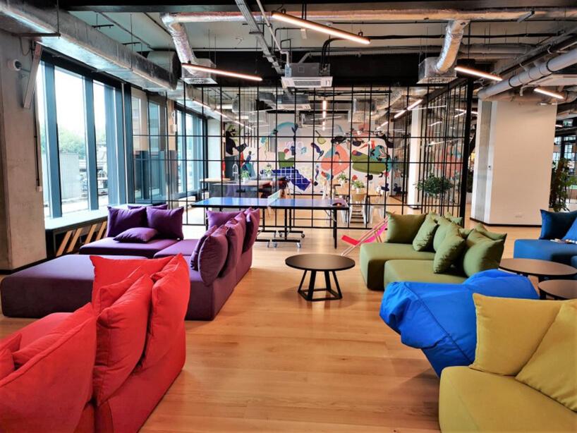 wnętrze Akademia LivinnX wKrakowie autorstwa Make It Yours oraz IMB Asymetria zkolorowymi siedziskami wpofabrycznych przestrzeniach