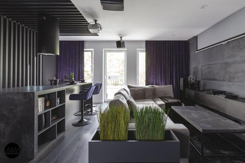 szare mieszkanie zaprojektowane przez pracownię Mandalinci Studio zbiałym sufitem ifioletowymi zasłonami