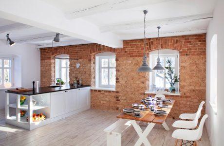 biała kuchnia połączona z salonem o ścianami z odsłoniętej cegły