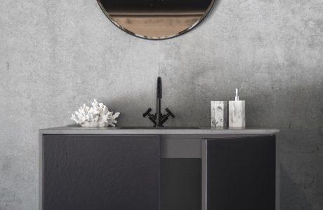 ciemno szara szafka łazienkowa z czarnym kranem i białymi dodatkami pod okrągłym lustrem