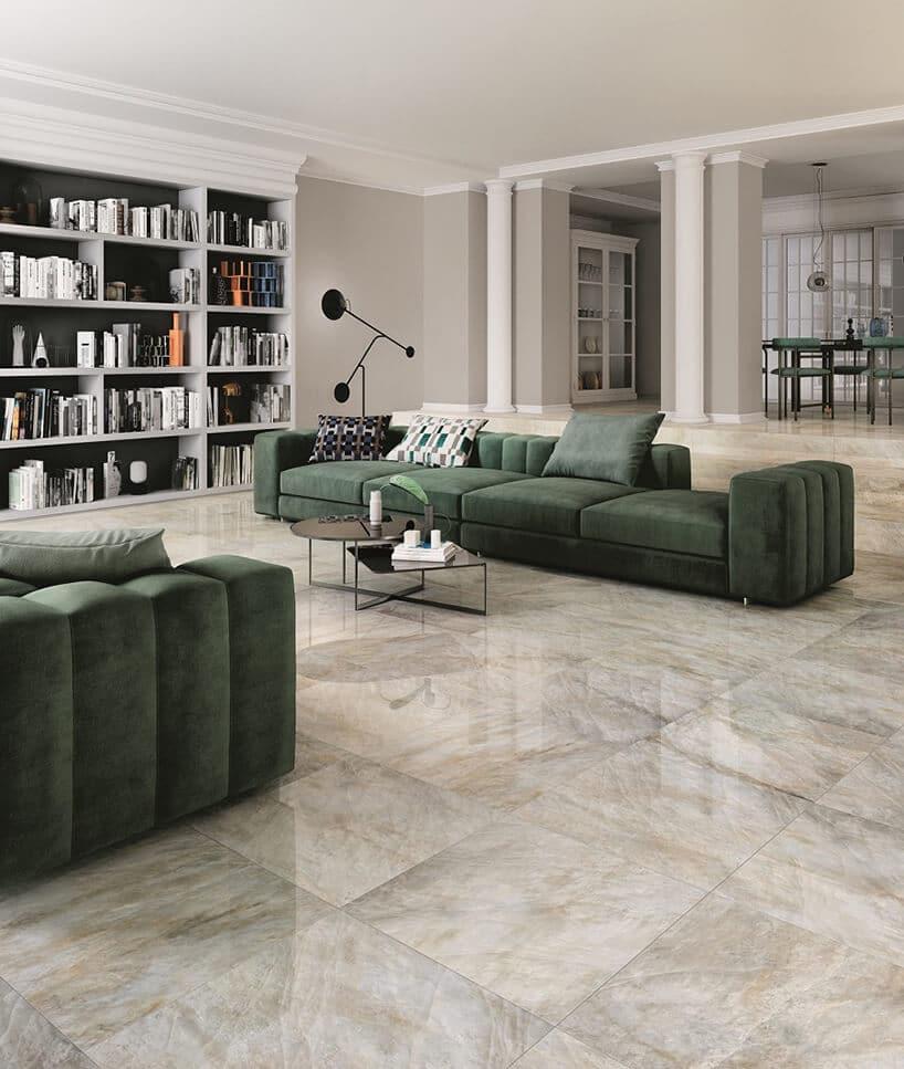 salon zmarmurową podłogą oraz butelkowo zielonym puszystymi kanapami