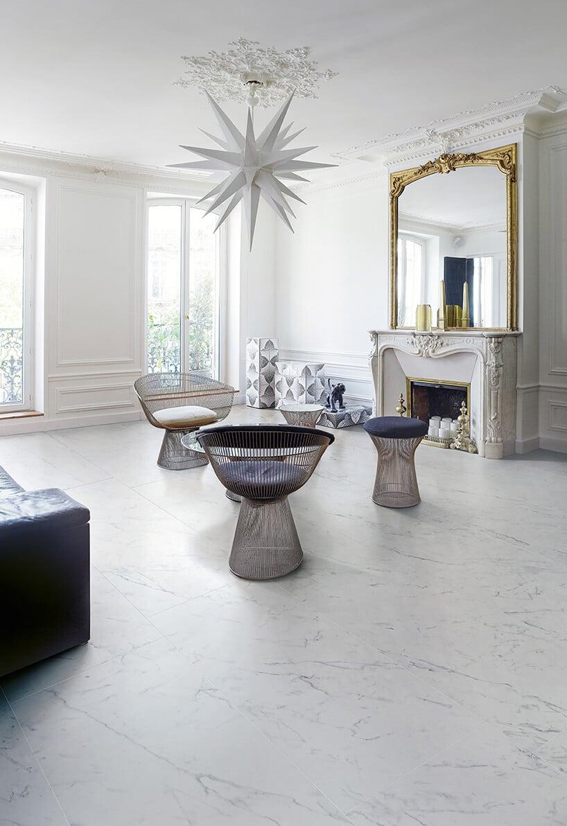 chłodny pokoj zkafelkami marmurowymi na podłodze oraz zdobieniami na ścianach białych
