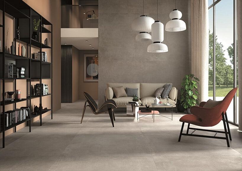 pomieszczenie zszarymi dużymi płytami na podłodze oraz stylowymi fotelami obitymi kolor brązu