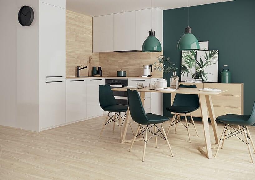 nwooczesne wnętrze kuchni zkrzesłami zielono butelkowym obiciem idodatkami wkolorze zielonym iipłytkami ceramicznymi na podłodze