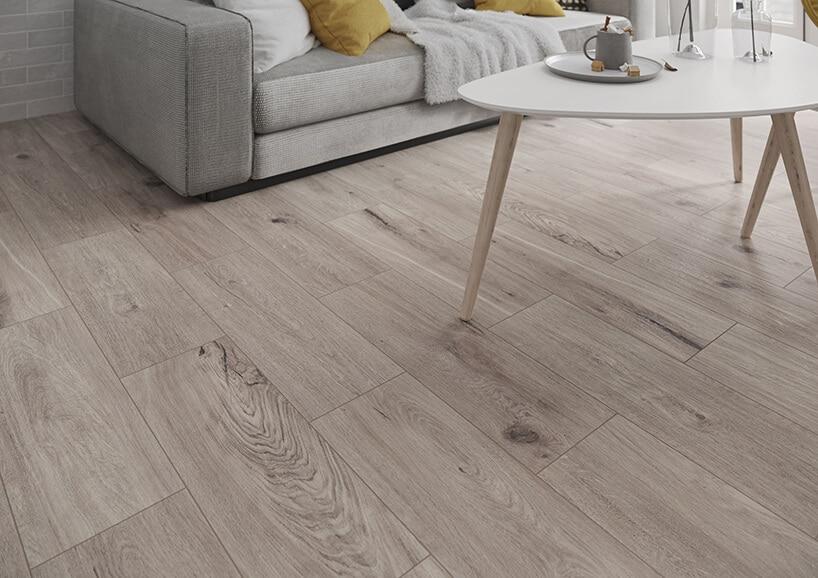 drewniana podłoga imitowana przez płytki ana nich szara materiałowa kanapa