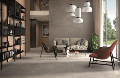 salon z szarymi dużymi płytami na podłodze oraz stylowymi fotelami obitymi kolor brązu
