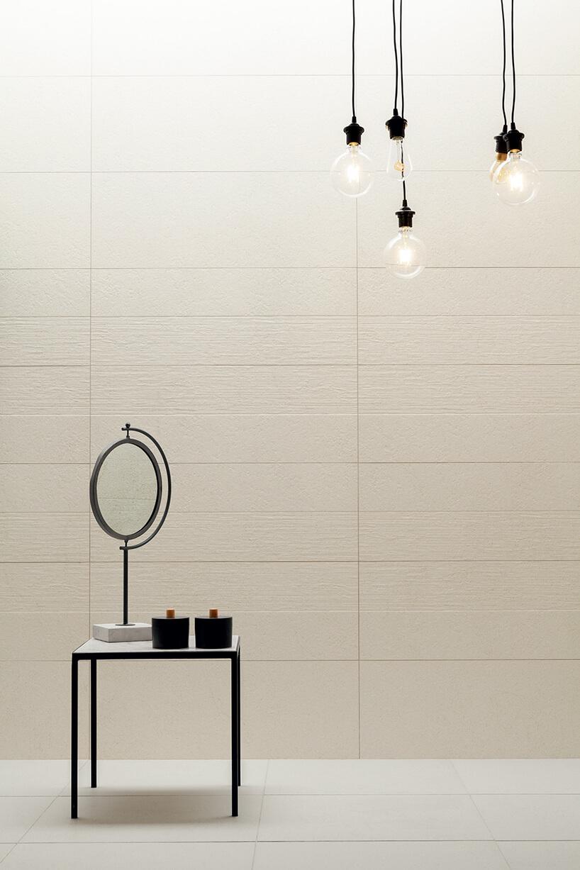 strukturalne płytki ceramiczne Tubądzin jako tło dla czarnego stolika iczarnego lustra
