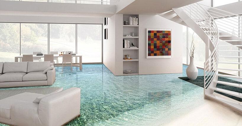 białe wnętrze salonu zzakręconymi schodami oraz podłogą zgrafiką morza