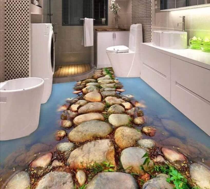 łazienka zbiałymi meblami iciemnymi kafelkami oraz kamieniami na podłodze