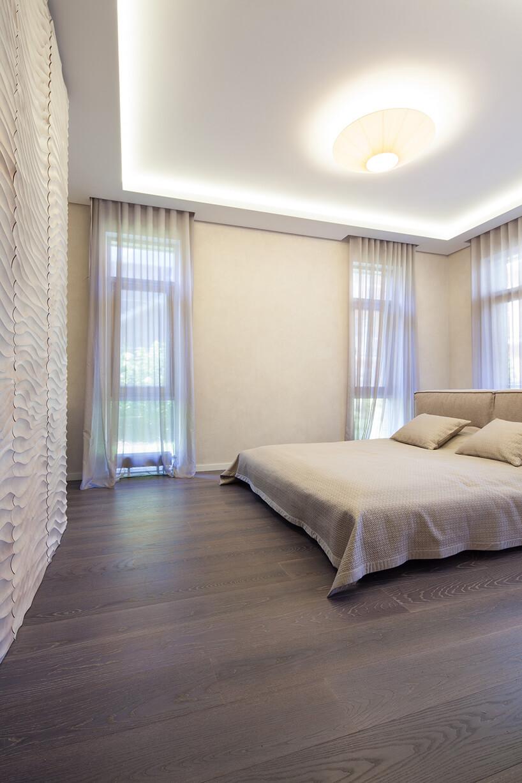 ciemna podłoga od kaczkan wjasnej sypialni zdużym łóżkiem