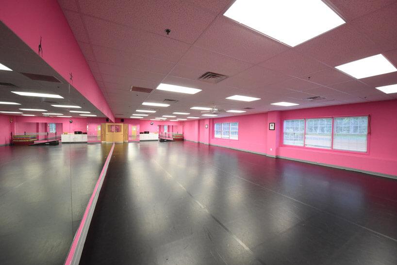 różowa sala do tańczenia zszarą podłogą iprzeszkleniem