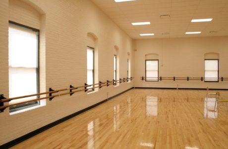 lśniący parkiet w sali tanecznej z dużymi oknami