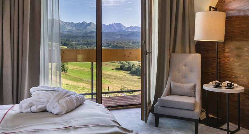 beżowy fotel pościel biały stoliczek elegancka lampa na tle ciemno drewnianej ściany szarej podłogi ipięknego widoku zotwartego balkonu
