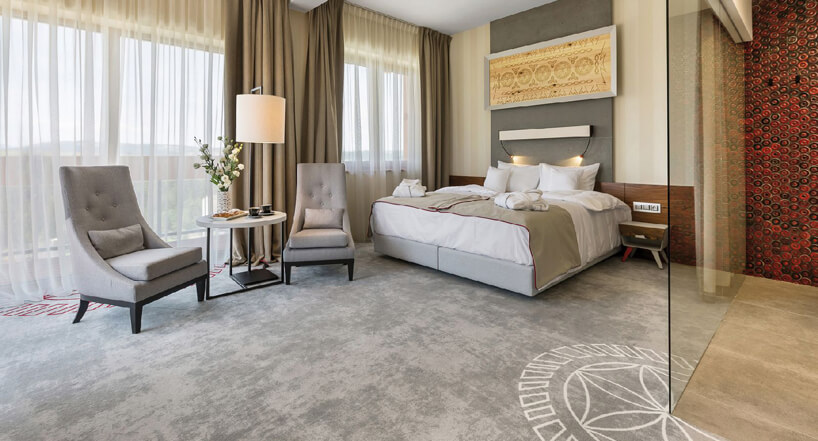 łóżko malżeńskie beżowe fotele biały stoliczek lamapa beżowe ibiałe firanki wdużym pokoju na szarej podłodze