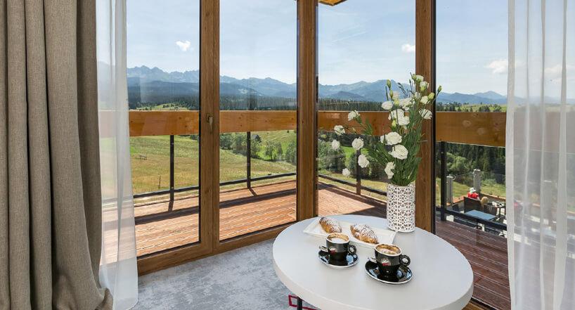 biały stolik zfiliżankami na szarej podłodze na tle okien zpięknym widokiem gór