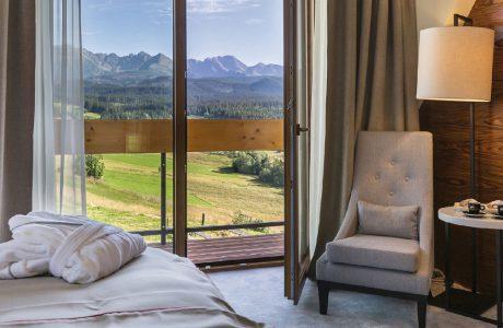 beżowy fotel pościel biały stoliczek elegancka lampa na tle ciemno drewnianej ściany szarej podłogi i pięknego widoku z otwartego balkonu