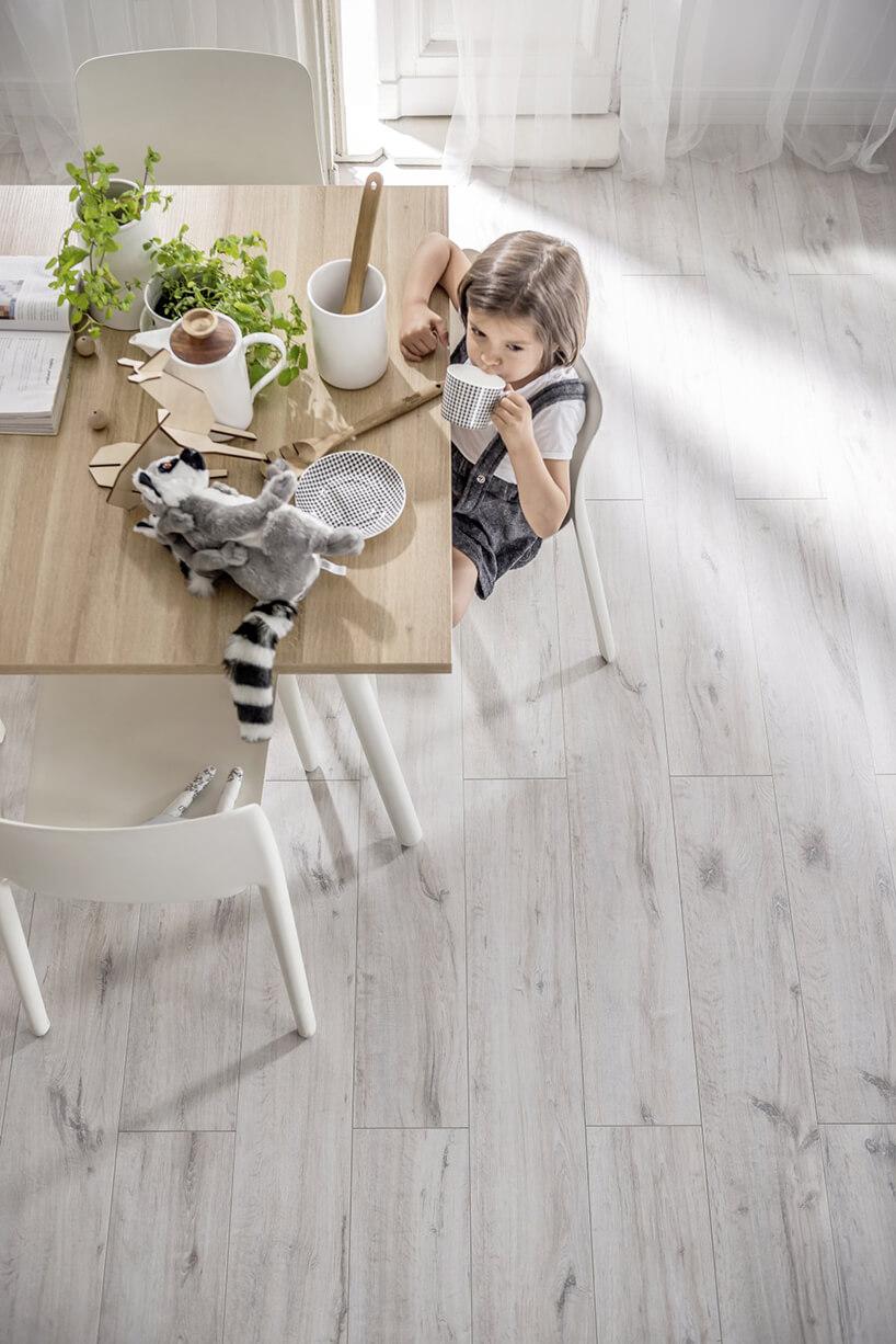 chłopiec jedzący śniadanie na drewnianym stole zbiałymi nogami na szarej podłodze VOX