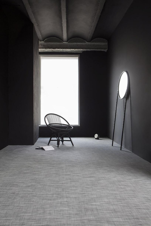szara wykładzina winylowa od Newmor wciemnym wnętrzu zczarnym krzesłem iopartym ościanę lustrze