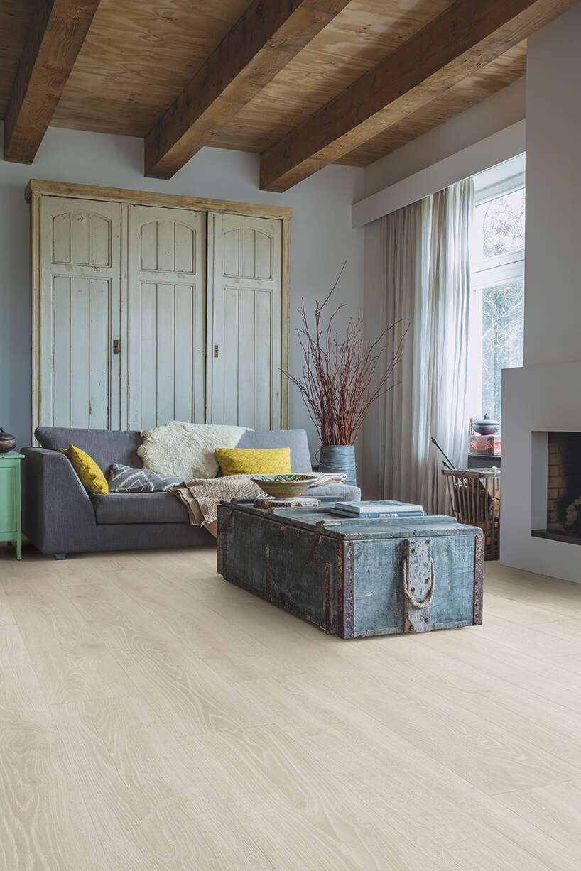 jasne podłoga laminowana Quick-Step wsalonie wze starą niebieska skrzynią przerobioną na stolik obok komina