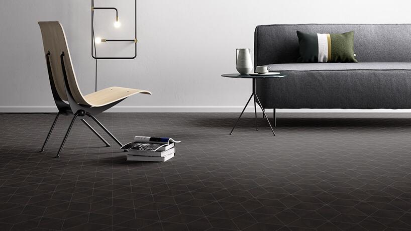 ciemna podłoga winylowa wgeometryczne kształty pod szarą sofą imetalowo-drewnianym nowoczesnym krzesłem