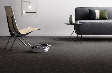 ciemna podłoga winylowa w geometryczne kształty pod szarą sofą i metalowo-drewnianym nowoczesnym krzesłem