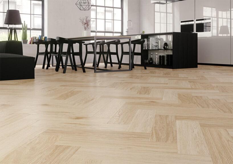 czarne meble wdużym pomieszczeniu zjasnymi ścianami oraz drewnianą podłogą