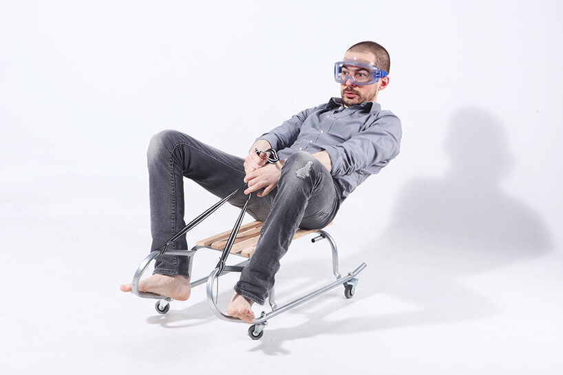 zdjęcie projektanta Szymona Hanczara siedzącego na sankach na kółkach