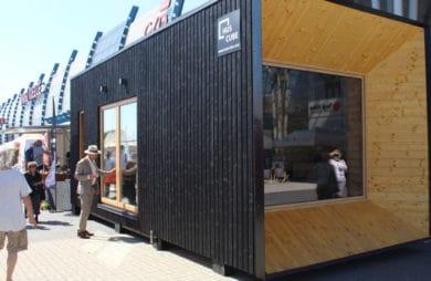 duży domek z czarnego kontenera z elementami drewna