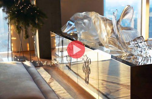 elegancka szafka z błyszczącym metalowym frontem o szklanymi dekoracjami na górze