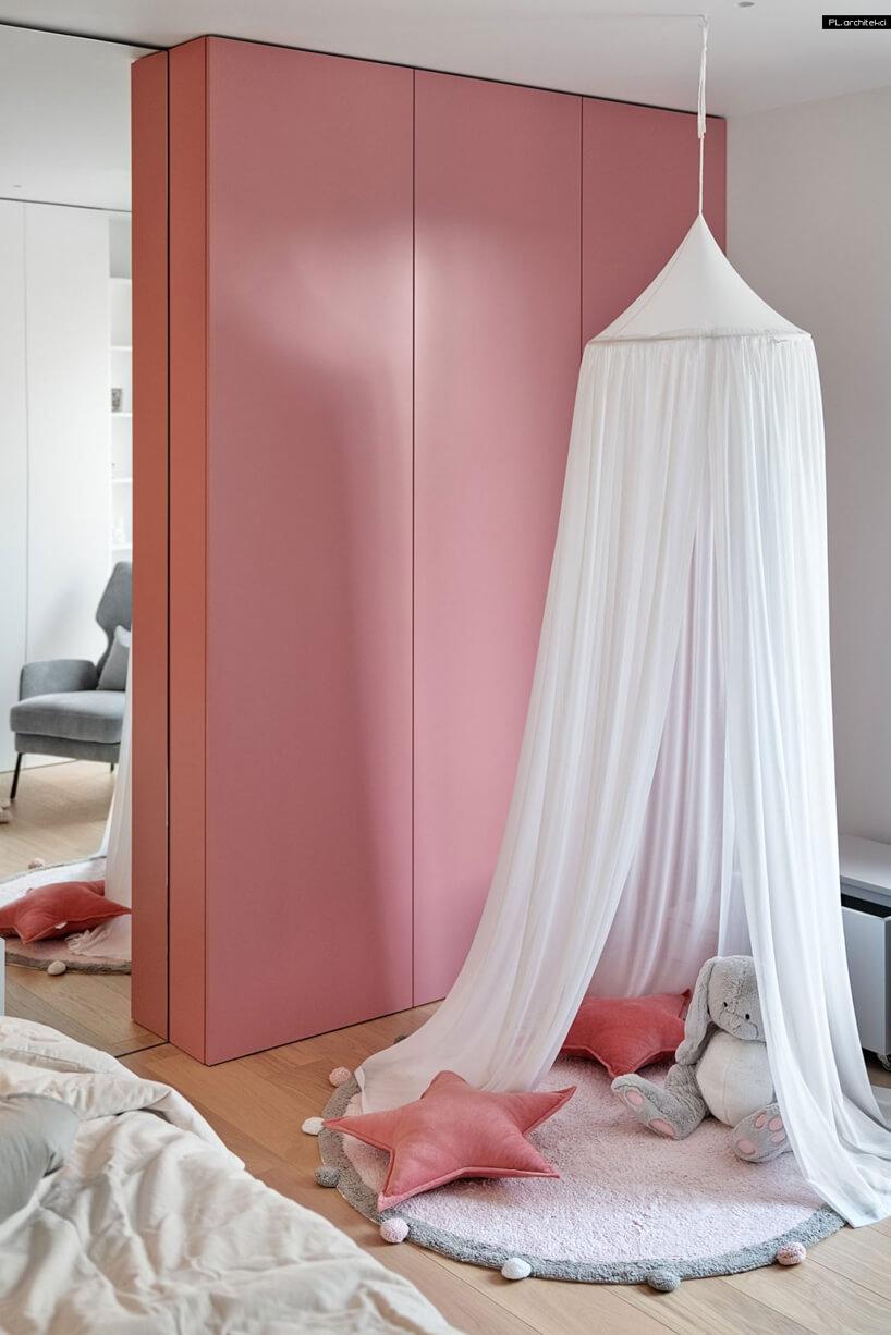 jasny pokój dziewczynki zwysokim lustrem obok różowej szafy jako tło białym zwisającym materiałem