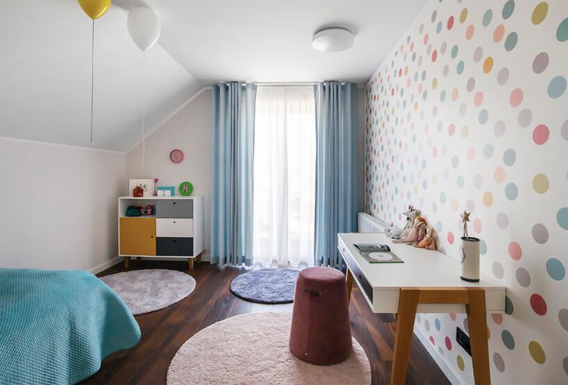 biały pokój dla dziewczynki na poddaszu zciemną drewniana podłogą itapetą wkolorowe kółka
