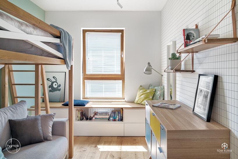 jasny pokój dziecięcy zdrewnianym łóżkiem na antresoli nad szarą sofą